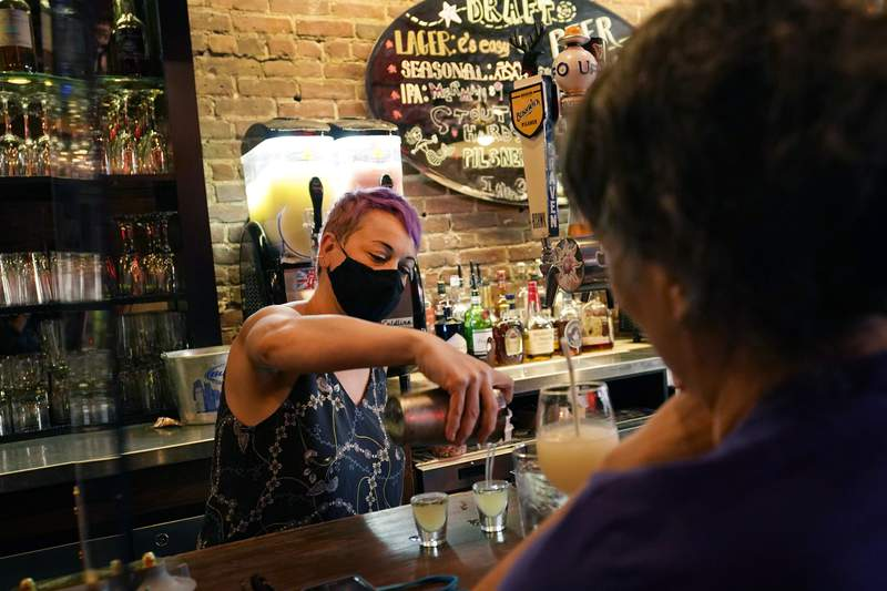 Erin Bellard, co-owner of e's Bar on Manhattan's Upper West Side, pours shots for two regulars during happy hour, Monday, May 17, 2021, in New York. (AP Photo/Kathy Willens)