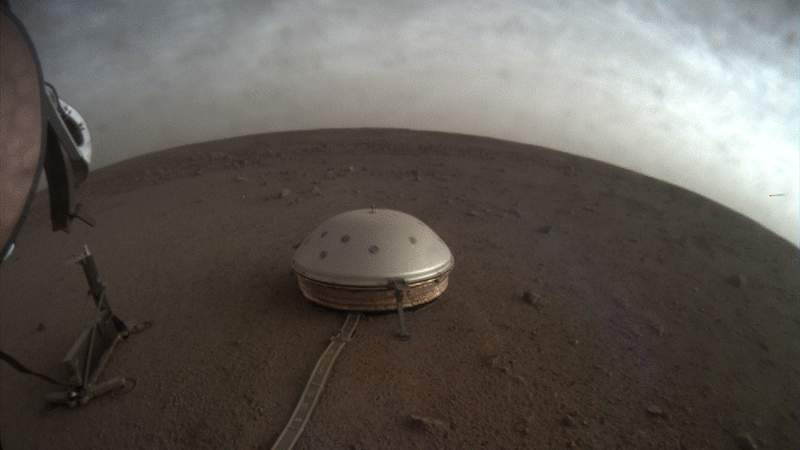 In this undated photo made available by NASA on Thursday,  July 22, 2021, clouds drift over the dome-covered SEIS seismometer of the InSight lander on the surface of Mars. The quake-measuring device is providing the first detailed look at the red planets interior, revealing a surprisingly thin crust and a molten core. In a series of articles published in July 2021, scientists reported that the Martian crust is within the thickness range of Earths. Mars mantle, meanwhile, is roughly half that of our own much bigger planet, while the core _ measured from the dusty surface to dead center _ is more than 1,000 miles smaller. (NASA/JPL-Caltech via AP)