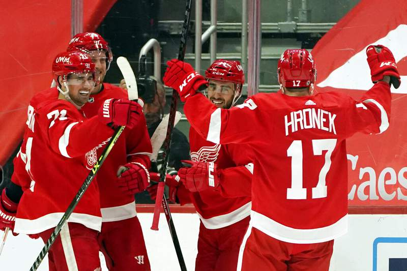 Detroit Red Wings center Dylan Larkin (71), right wing Anthony Mantha (39) and defenseman Filip Hronek (17) congratulate center Robby Fabbri (14) after his hat-trick during the third period of an NHL hockey game against the Dallas Stars, Thursday, March 18, 2021, in Detroit. (AP Photo/Carlos Osorio)