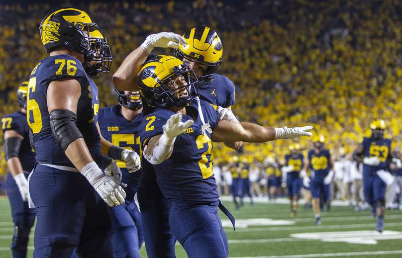 Michigan running back Blake Corum (2) celebrates a touchdown with teammates during the fourth quarter of an NCAA college football game against Washington in Ann Arbor, Mich., Saturday, Sept. 11, 2021.