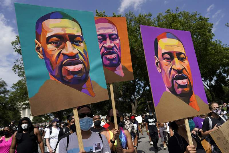 FILE - In this Aug. 28, 2020, file photo, people carry posters with George Floyd on them as they march from the Lincoln Memorial to the Martin Luther King Jr. Memorial in Washington. (AP Photo/Carolyn Kaster, File)