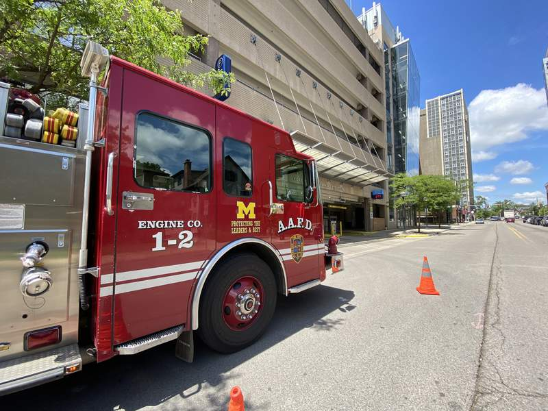 An Ann Arbor Fire Department truck is parked outside the Forest Avenue Parking Structure, where wet drills are taking place on June 3, 2021. In the distance, more trainings are taking place at University Towers.