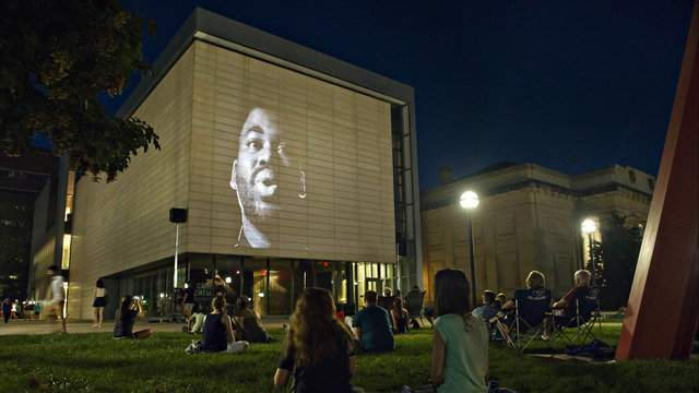 Onlookers sit on the grass to watch an installation at the first UMMA 'Nights' event (Photo: UMMA)