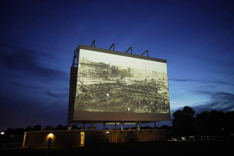 """FILE - In this Wednesday, May 26, 2021 file photo, an image of devastation from the Tulsa Race Massacre is shown on a drive-in movie screen from the documentary """"Rebuilding Black Wall Street,"""" during a screening of documentaries for centennial commemorations of the destruction of the Black neighborhood in Tulsa, Okla. (AP Photo/John Locher)"""
