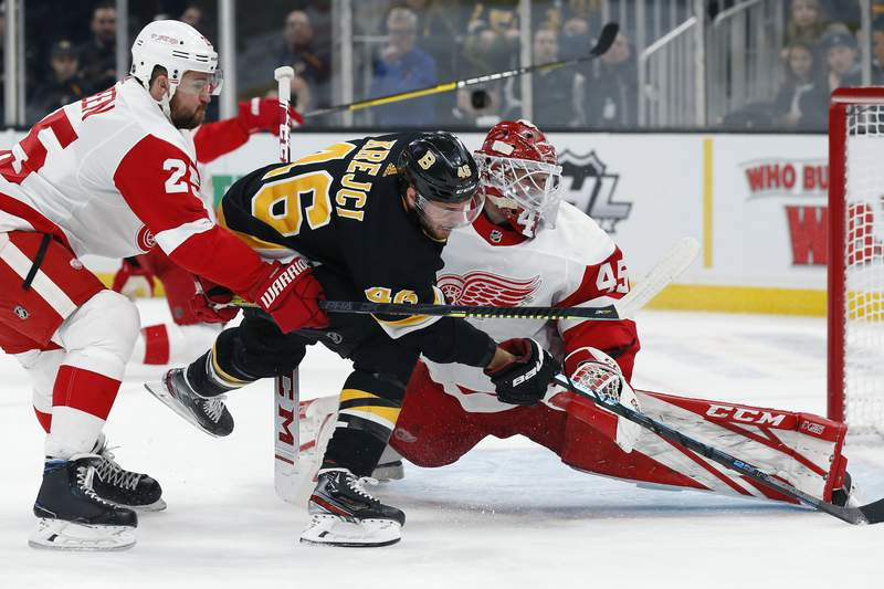 Boston Bruins' David Krejci (46) chases the puck after his shot was blocked by Detroit Red Wings' Jonathan Bernier (45) during the second period of an NHL hockey game in Boston, Saturday, Feb. 15, 2020. (AP Photo/Michael Dwyer)