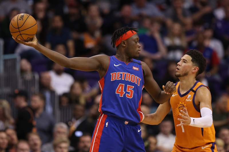Sekou Doumbouya #45 of the Detroit Pistons handles the ball against Devin Booker #1 of the Phoenix Suns during the second half of the NBA game at Talking Stick Resort Arena on February 28, 2020 in Phoenix, Arizona.