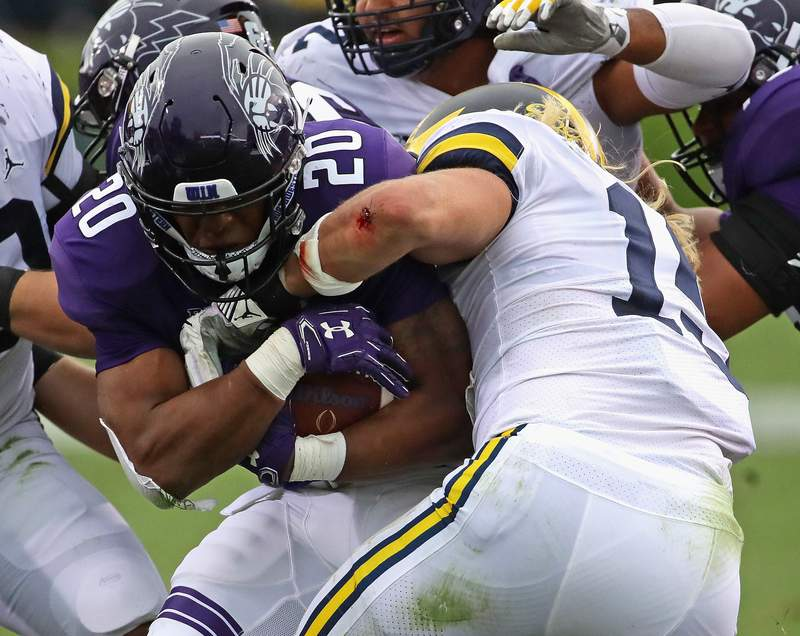John Moten IV #20 of the Northwestern Wildcats is stopped by Chase Winovich #15 of the Michigan Wolverines at Ryan Field on September 29, 2018 in Evanston, Illinois.