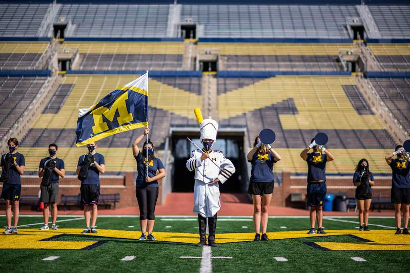 A small number of Michigan Marching Band members pose at the empty Michigan Stadium during a photoshoot.