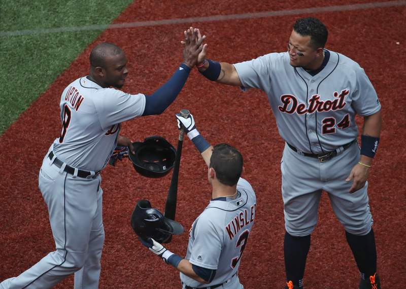Justin Upton #8 of the Detroit Tigers is congratulated by Miguel Cabrera #24 and Ian Kinsler #3 after scoring a run in the fourth inning during MLB game action against the Toronto Blue Jays on July 9, 2016 at Rogers Centre in Toronto, Ontario, Canada.