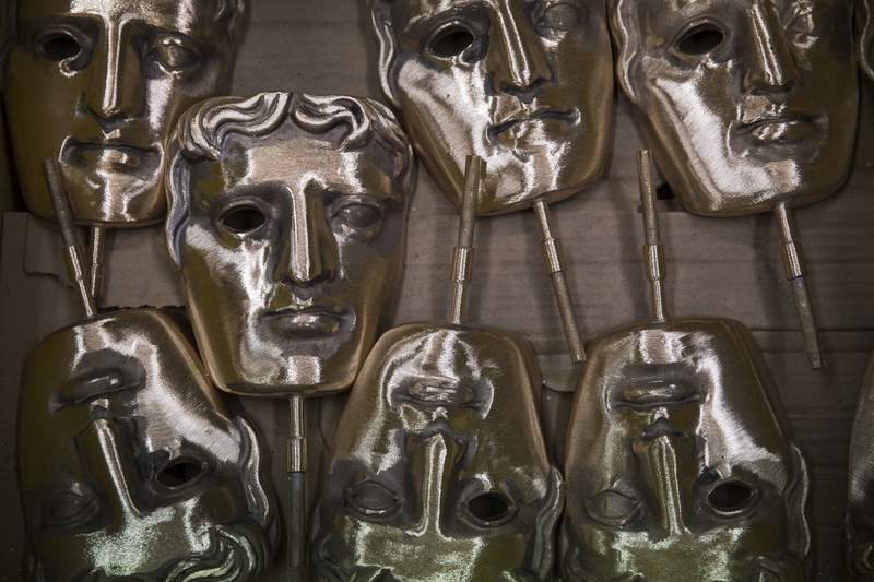 FILE - In this Tuesday, Jan. 31, 2020 file photo, bronze alloy masks lie in a foundry in West Drayton, Middlesex,  ahead of the awards ceremony in February. Next years British Academy Film Awards have been postponed by two months, organizers said Tuesday, June 16, 2020. The move follows a decision by Hollywoods film academy to shift the 2021 Oscars from February to April because of the coronavirus pandemic. (Photo by Joel Ryan/Invision/AP, File)