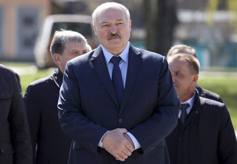 FILE - In this Monday April 26, 2021 file photo, Belarus President Alexander Lukashenko, accompanied by officials, attends a requiem rally on the occasion of the 35th anniversary of the Chernobyl disaster in the town of Bragin, some 360 km (225 miles) south-east of Minsk, Belarus. Raman Pratasevich, a founder of a messaging app channel that has been a key information conduit for opponents of Belarus authoritarian president, has been arrested after an airliner in which he was riding was diverted to Belarus because of a bomb threat. The presidential press service said President Alexander Lukashenko personally ordered that a MiG-29 fighter jet accompany the Ryanair plane  traveling from Athens, Greece, to Vilnius, Lithuania  to the Minsk airport. (Sergei Sheleg/BelTA Pool Photo via AP, File)