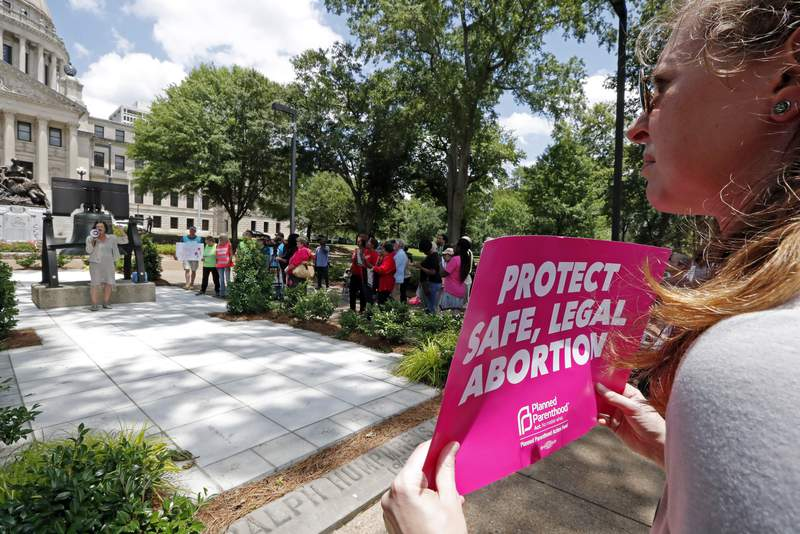 FILE - In this Tuesday, May 21, 2019 file photo, An abortion rights advocate holds a sign at the Capitol in Jackson, Miss. Republican lawmakers in at least a half dozen GOP-controlled states already are talking about copying a Texas law that bans abortions after a fetal heartbeat is detected. The law was written in a way that was intended to avoid running afoul of federal law by allowing enforcement by private citizens, not government officials. Democratic governors and lawmakers are promising to take steps to protect abortion rights, after the U.S. Supreme Court allowed the Texas law to stand. (AP Photo/Rogelio V. Solis, File)
