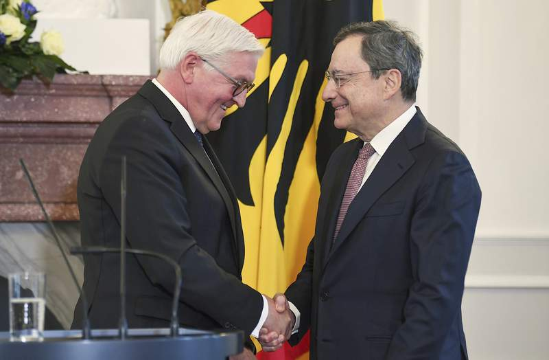 German President Frank-Walter Steinmeier, left, and the former President of the European Central Bank (ECB), Mario Draghi, right, shake hands at the Bellevue Palace in Berlin, Germany, Friday, Jan. 31, 2020. Mario Draghi has been awarded Germany's highest honor. It was a recognition of his central role in helping preserve Europe's single currency that has met with some criticism in the eurozone's biggest economy.  (Britta Pedersen/dpa via AP)