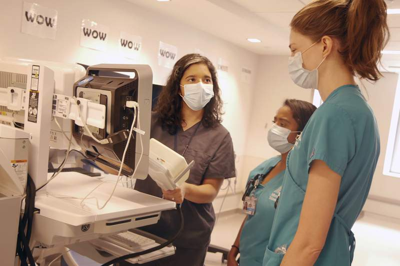 In this August 2020 photo provided by the Mount Sinai Health System, neurologist Dr. Alexandra Reynolds holds part of a device that tracks blood flow in the brain, at a hospital in New York. Reynolds was checking comatose COVID-19 patients for signs of a stroke when she stumbled onto a new clue about how the coronavirus may harm the lungs - thanks to a test that uses tiny air bubbles and a robot. (Mount Sinai Health System via AP)