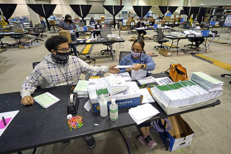 Harris County election workers Jose Vasquez, left, and Romanique Tillman prepare mail-in ballots to be sent out at election headquarters Tuesday, Sept. 29, 2020, in Houston. (AP Photo/David J. Phillip)