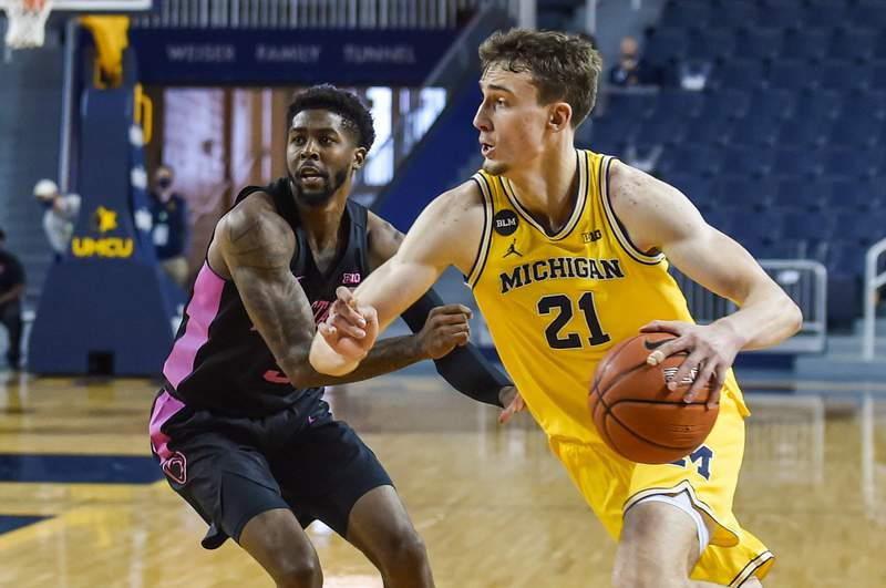 Franz Wagner #21 of the Michigan Wolverines dribbles the ball past Jamari Wheeler #5 of the Penn State Nittany Lions during the second half of a college basketball game at Crisler Arena on December 13, 2020 in Ann Arbor, Michigan. The Michigan Wolverines won the game 62-58.