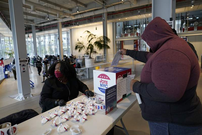 A voter drops his absentee ballot into a box at a special table set aside for that purpose on the last day of early voting, Sunday, Nov. 1, 2020, at Columbia University's Forum in the West Harlem neighborhood of New York. (AP Photo/Kathy Willens)