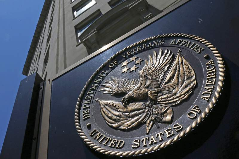 FILE - This June 21, 2013, file photo, shows the seal affixed to the front of the Department of Veterans Affairs building in Washington.  In a federal lawsuit filed this week, U.S. Navy veteran from South Carolina says he ended up with full-blown AIDS, because government health care workers never informed him of his positive test result in 1995. He says the test was done as part of standard lab tests at a U.S. Department of Veterans Affairs medical center in Columbia, South Carolina. A V.A. spokeswoman says the agency typically does not comment on pending litigation. (AP Photo/Charles Dharapak, File)