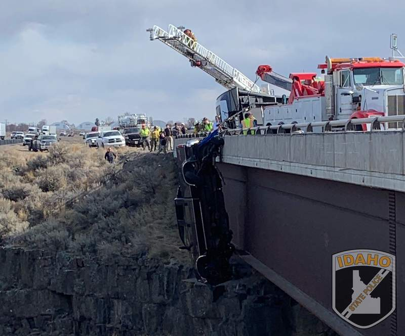 This image provided by the Idaho State Police shows the scene where authorities say a set of camp trailer safety chains and quick, careful work by emergency crews saved two people after their pickup truck plunged off a bridge, leaving them dangling above a deep gorge in southern Idaho on Monday, March 15, 2021. (Idaho State Police via AP)