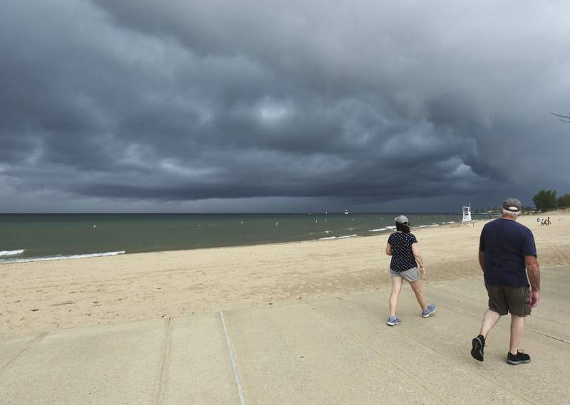 A couple stroll along Silver Beach in St. Joseph, Mich., Wednesday, June 10, 2020, as a storm moves over Lake Michigan.(Don Campbell/The Herald-Palladium via AP)