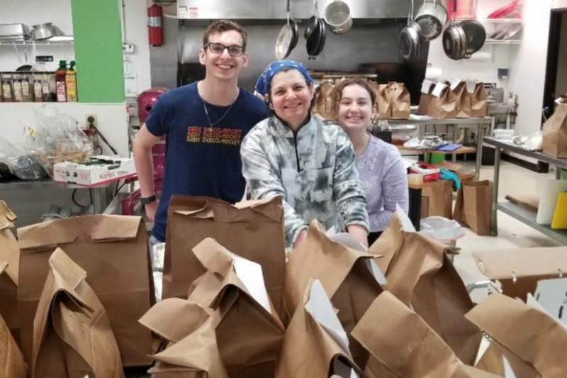 Stacy Williams (center) with meals ready to be delivered to Peace Neighborhood Center.