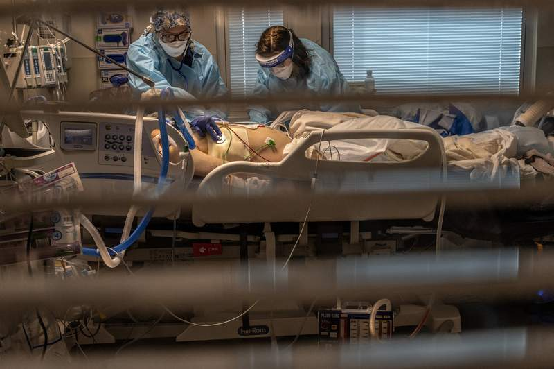 """Phlebotomist lab assistant Jennifer Cukati, right, and Registered Nurse Carina Klescewski, left, care for a COVID-19 patient inside the Sutter Roseville Medical Center ICU in Roseville, Calif., on Tuesday, Dec. 22, 2020. The patient came in the night before """"code blue"""" and COVID-19 positive. His heart stopped and he had to be intubated, and is on a respirator. (Renee C. Byer/The Sacramento Bee via AP, Pool)"""